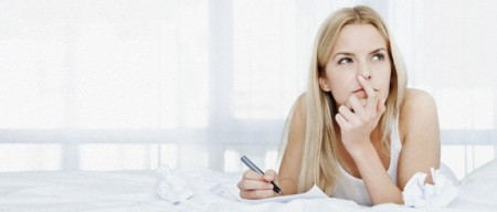 Young blonde woman writing  letter in bed