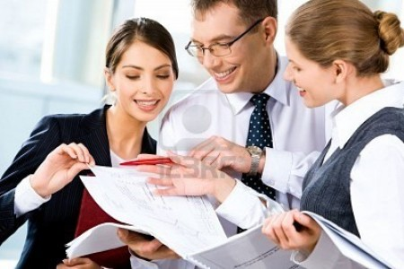 image-of-three-happy-business-people-looking-at-business-plan-with-smiles