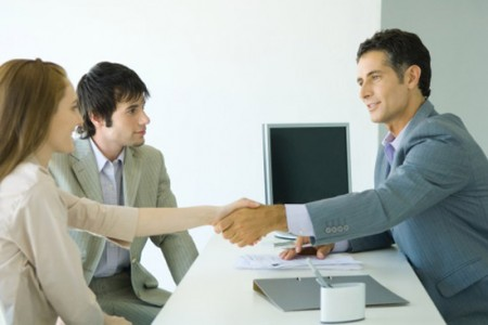 Young couple sitting across desk from businessman, woman shaking hands with businessman, side view