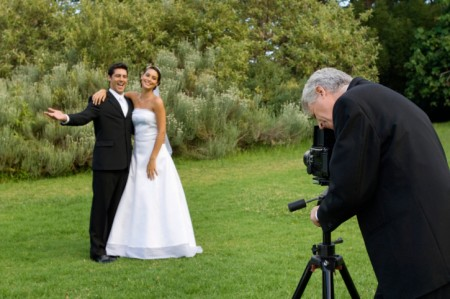 Photographer taking picture of bride and groom