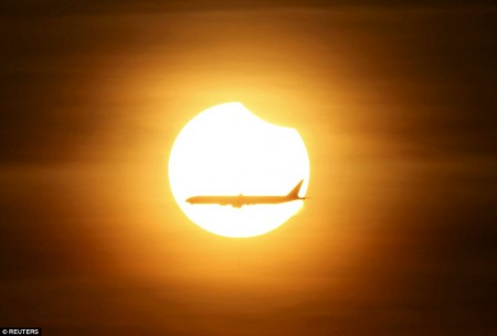 3203203E00000578-3482995-An_aeroplane_flies_past_the_sun_as_it_goes_into_a_partial_solar_-a-4_1457509410391