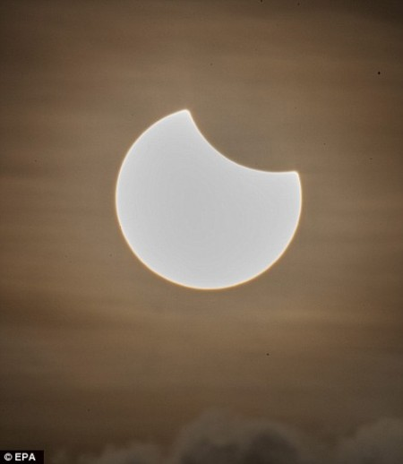 3203573700000578-3486697-A_partial_solar_eclipse_is_pictured_above_a_cloud_formation_at_d-m-63_1457651147501